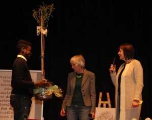 Henning Lendo Sukama überreicht den Preis  an Frau Reinig - eine weiße Rose, die fortan im Klick Kindermuseum Wurzeln schlagen wird
